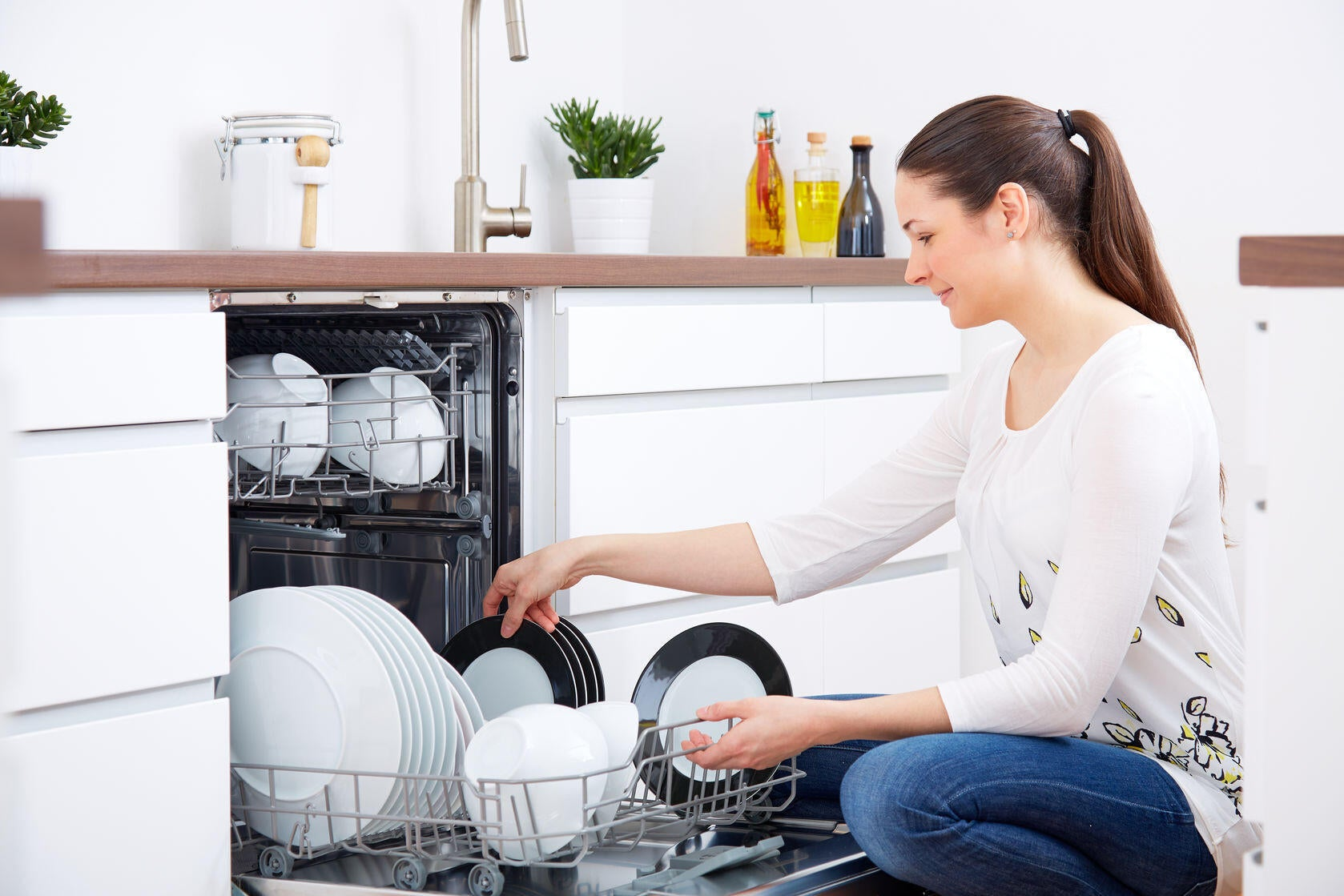 Woman unloading dishwasher