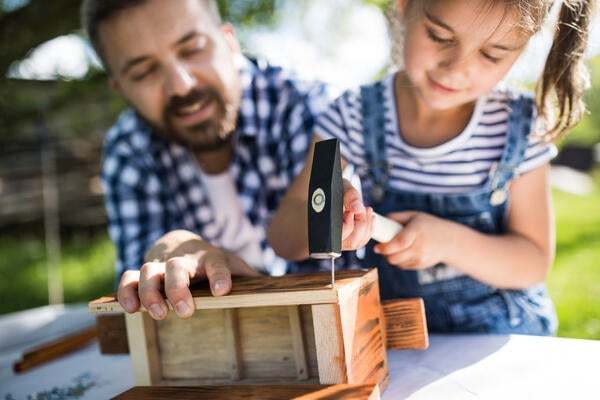 Father helping daughter with birdhouse