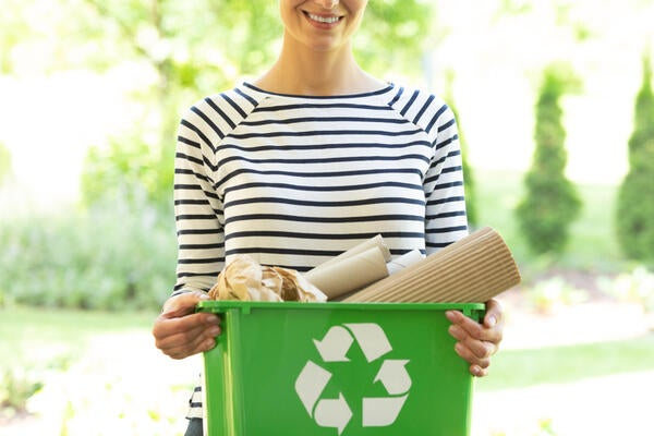 Smiling woman holding a recycling bin