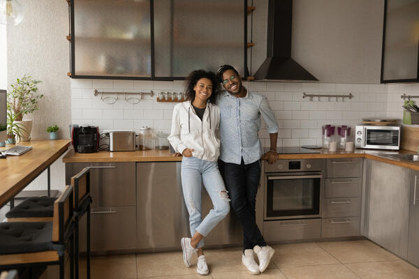 Young couple smiling in their kitchen