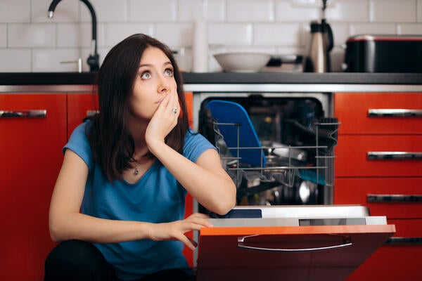 Woman pondering if she should repair or replace a broken dishwasher
