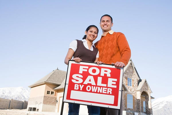 Couple holding For Sale by Owner Sign