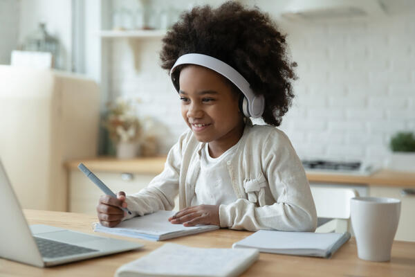 Child at a table with laptop