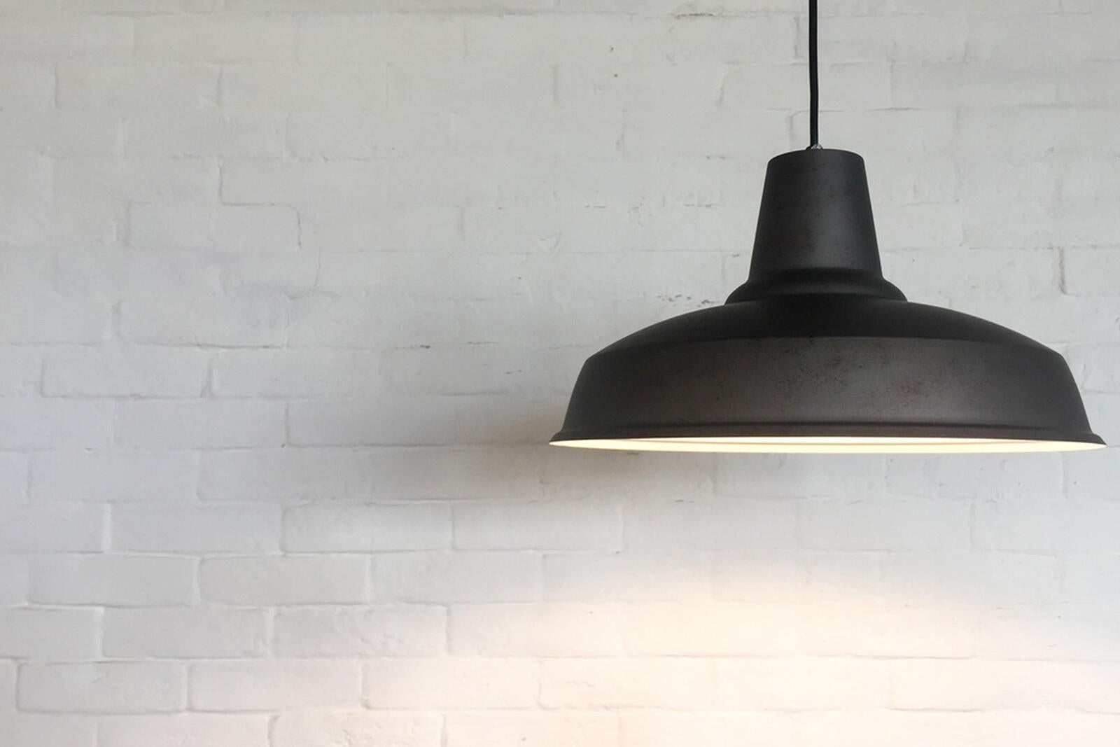 A hanging barn-style light fixture turned on