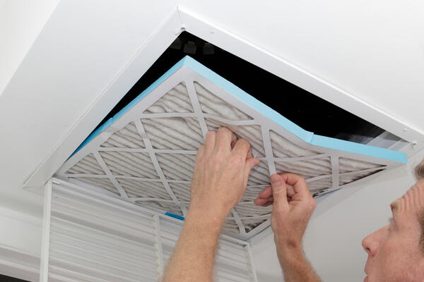 Person removing an old dirty air filter from a ceiling intake vent of a home HVAC system.