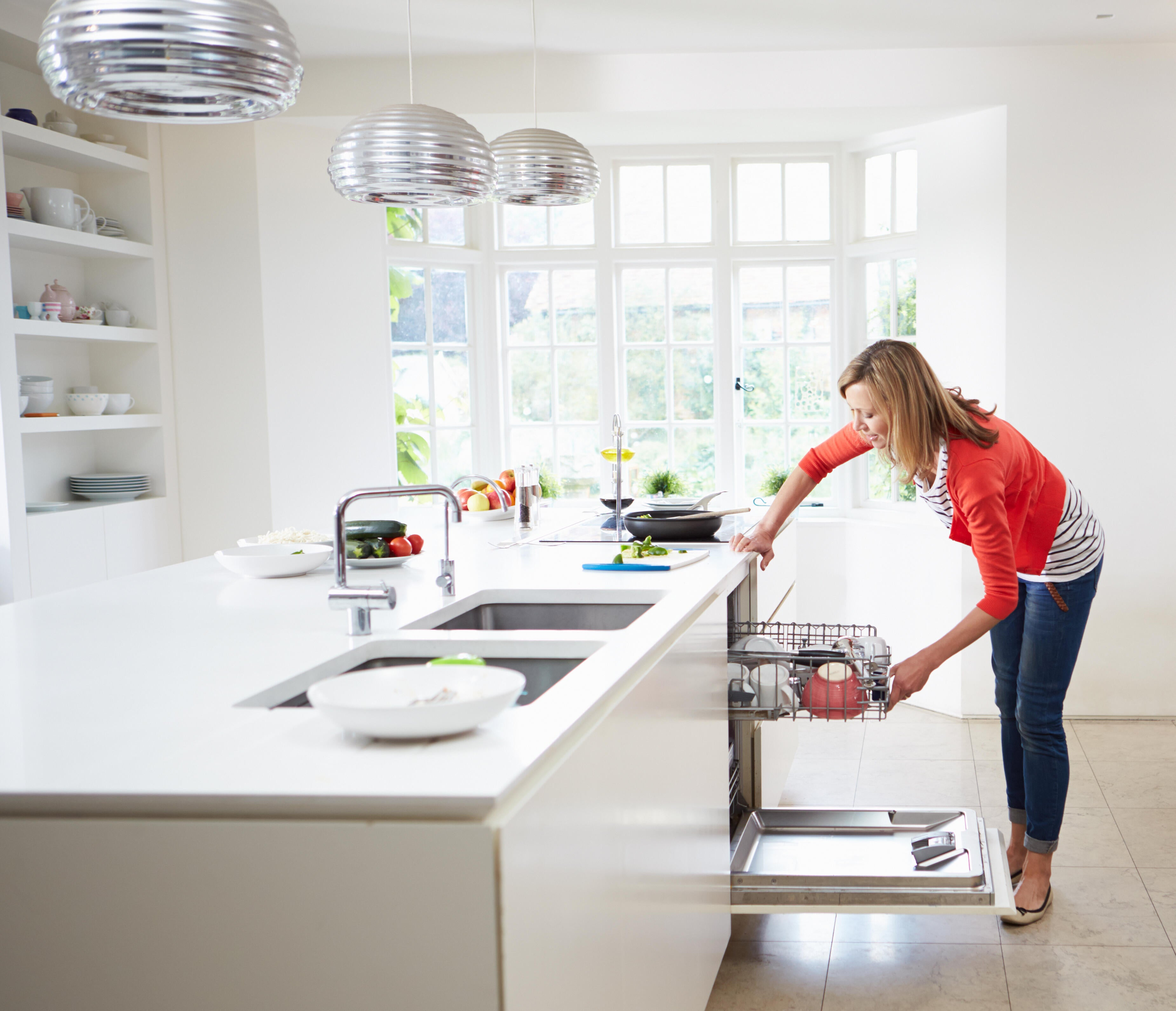 Woman in kitchen with open dishwasher